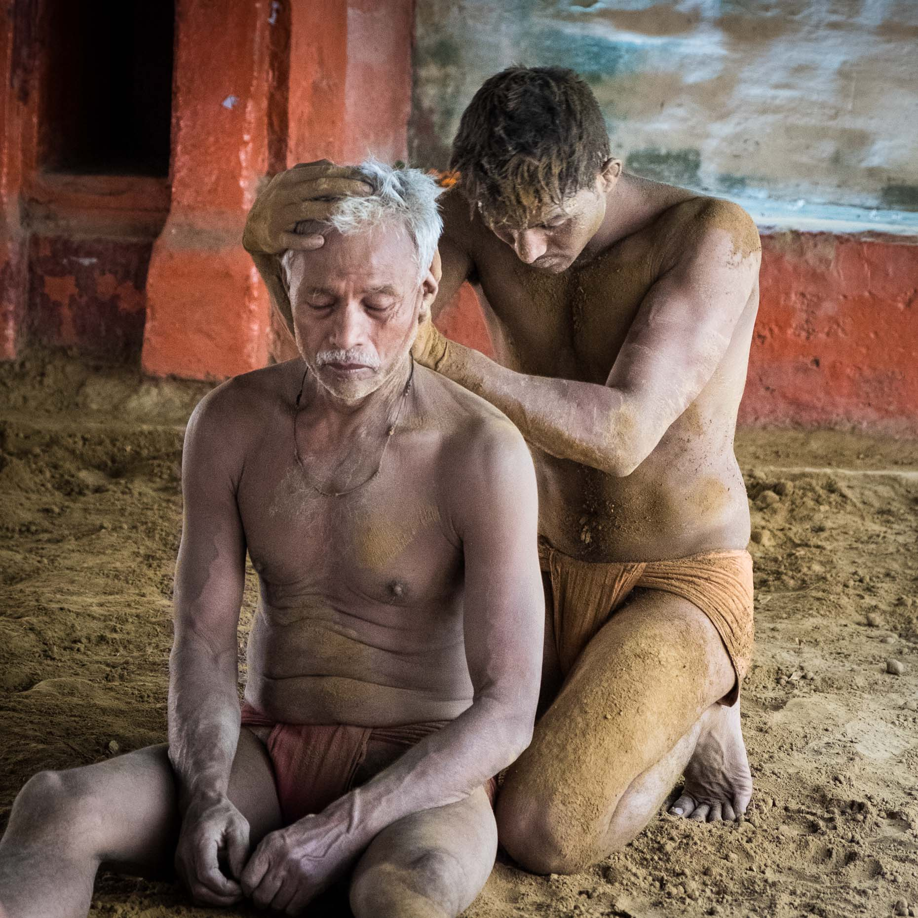 HEALING HANDS: a wrestling student massages his mentor after practice in Varanasi, India